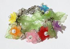 Bracelet avec fleurettes multicolores des feuilles vertes pales et des perles blanches