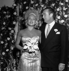 Lana Turner and fourth husband Bob Topping were married in 1948 and divorced in 1952.  She wore dress of champagne satin and lace. Look at all those gardenias in the backdrop!  She married and divorced four more times!
