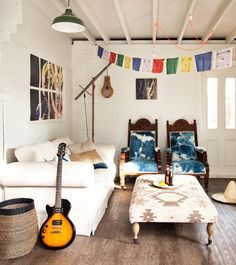 Bohemian living room with blue chairs and colorful flag banner hanging above ottoman #currentvibes #currentlycoveting