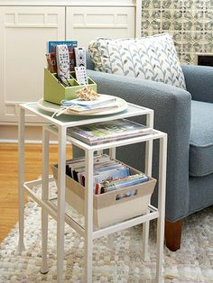 Nesting tables are perfect for squeezing a lot of storage out of minimum space. Pull out the lower table when you need an extra surface for holding drinks or reading material, then tuck it away when you're done. Here, a stylish fabric-covered bin keeps DVDs accessible but contained.
