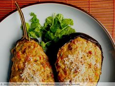 Stuffed Eggplants: 2 medium or 1 large eggplant  Olive oil (for sprinkling)  Salt and pepper, to taste  2 tbsp olive oil  ½ tsp ground coriander  ½ tsp ground cumin  1 clove garlic, finely chopped  2 medium ripe tomatoes, coarsely chopped  1 bay leaf  1 cup paneer or whole milk ricotta (I used crumbled paneer)  1/3 cup finely grated parmesan  1 tbsp chopped fresh cilantro  2 sausages or 2 slices ham, finely diced, or omit this if you're vegetar