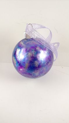 This is a colorful 2.5 inch inked glass ornament. It was inked on the outside is was inked with blue, silver and purple. It has its own unique design and wont find another like it. This would be a cute ornament for your Christmas tree or to give as a gift to a family, friend or even a co-worker.  It is glass so can be breakable so always be cautious. The paint is on the inside and the ink has been sealed for an easy wipe down to clean. The top is glued to ensure it stays on.  Colors may vary…