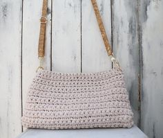 Elegant summer beige handcrafted bag, which made by 100% cotton yarn.   It also features a beautiful long strap made by natural cork with gold details.  It's length is adjustable with gilded metal fastener.  The connective rings have easy openings so to facilitate all choices of strap changes, even with a shorter one.    The interior is covered by a refined beige cotton lining, whereas a magnetic clasp keeps it closed.     Height  24cm Length  42cm   Price: 150€