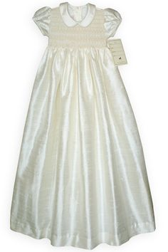 A truly sumptuous smocked Christening gown of ivory silk dupioni lavishly embroidered with bullion roses and hand embroidery. Long sash for a bow in the back. Matching smocking and embroidery adorn the silk bonnet. Under slip included. A beautiful creation for your little angel special day!