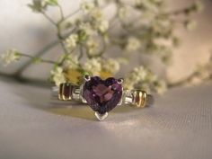 Heart cut amethyst & diamond ring in 10k white gold. This one is just such a pretty and elegant ring. Featuring a setting in 10k white gold, with two gold accents aside the diamond accents. $179.50