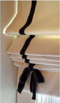 Estor plegable con tela lisa y aplicaciones verticales pespunteadas, acabadas en lazo.