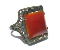 Wonderful antique carnelian ring with marcasite accent stones and a filigree style profile with a floral design. Marked sterling on the inside of the band. Size 5.25 Check out Ribbons Edge for more great pieces of vintage and antique jewelry