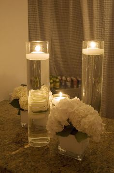 White hydrangeas look beautiful next to candles floating in tall vases.