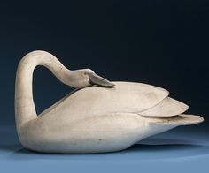 """M.J. Gray (Maine, Twentieth Century). Carved and Painted Sleeping Trumpeter Swan Decoy - Branded """"M.J. GRAY / SACO - ME"""" within a rectangle. Height 12 inches, length 23 1/2 inches"""