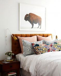 Mixed media pillows on white bed with buffalo artwork above headboard