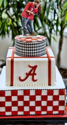I love the topper, even though we'd be in opposing jerseys. #Alabama Crimson Tide Grooms Cake in 3 tiers with groom kissing bride topper #housedividedheartsunited