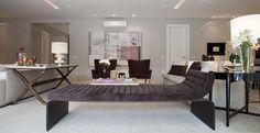 Na sala, parte dos móveis segue um design atual com linhas mais retas.Destaque para a  Tela abstrata da artista Flavia Brunetti que decora o living com tons que combinam com as poltronas e tapete.