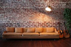 exposed brick, wood floors. Why o why did my landlord paint that wall? Also love that couch, light, and greenery.  Got to learn to play guitar. #decor #exposedbrick #industrial