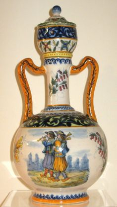 "HR Quimper Lidded Urn having two handles depicting two Breton musicians playing biniou and bombarde with anjoc & bruyere and decor riche motifs. Marked in scene and underneath HR Quimper 14 1/2""H c.1895-1922"