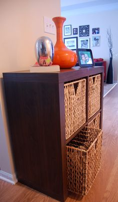 Expedit with baskets used to contain shoe clutter by the front door