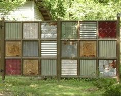 Outdoor privacy fence made w/old colored and plain tin squares.