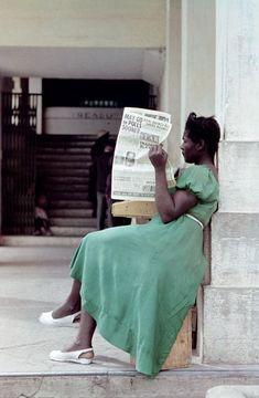 © Heinrich Heidersberger / www.heidersberger.de:   Eine Kubanerin in einem grünen Kleid sitzt mit ihrer Zeitung in einem Hauseingang. Havanna 1954.