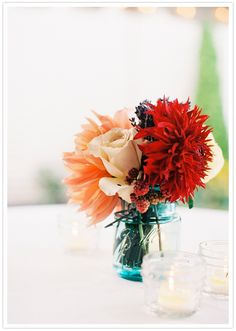 Mason jar centerpieces of roses, dinnerplate dahlias, and raspberries. Perfect for late summer.