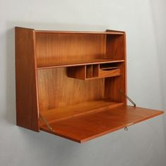 Dansk møbelproducent. Væghængt skrivebord/ reol af teaktræ, front med nedfældig klap, bag hvilken rum og lille skuffe. 1960'erne. H. 66 L. 90 B. 20 cm. Nøgle medfølger.