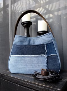 This handbag is handmade from upcycled/re-purposed denim jeans and lined with a beige and cream colored floral abstract designed canvas fabric. Handbag has a large front pocket with two interior pockets. For an added touch, the front is designed with a frayed patch pattern to make this a stand-out handbag. The strap is created from a brown leather strap with four rivets hammered on each side to reinforce the strap. This handbag is lined with a dense interfacing throughout the bag for…