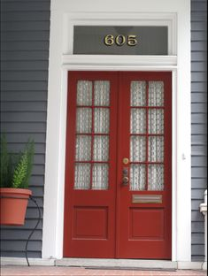 Gray house with red doors. (Outside to the yellow living room doors in 'Home is Where the...')
