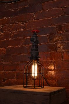 DESCRIPTION: This industrial light is flexible enough to work in a home, retail space, or office. It can work as a table light or on a night stand. The red spicket can be used on the top or switched with the steel plug on the side to switch up the look. There is an on/off switch on