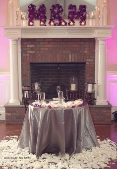 Sweetheart Table decor for a Purple, Lavender & Silver-grey wedding.  Custom flower initials 'M' on mantle made with a mix of purple & lavender carnations.