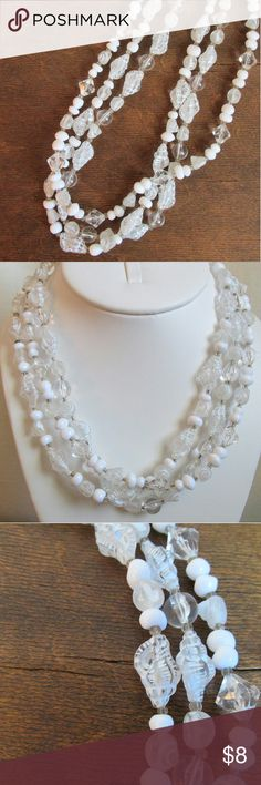 "3 strand white sea shell necklace 18"" Light and easy to wear this necklace is a summer must have. 3 strands of clear and white beads with she'll shaped beads. Measures 18"" long and is in good condition. The only thing I find is the spring ring clasp is a bit dark,see in last photo. Jewelry Necklaces"