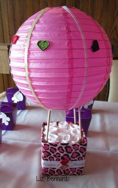 hot air balloon diaper cake bottom- small box wrapped in paper w/ wooden dowels. top is made from paper lantern. Decorated with buttons and ribbon with diapers inside box