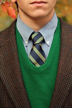 Green sweater blue shirt blue/yellow tie, brown jacked