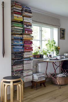 Sivupöydän vieressä on lattiasta kattoon ulottuva Paulan keitto-kirjojen kokoelma. Aputuoleina toimivat Alvar Aallon suunnittelemat jakkarat.