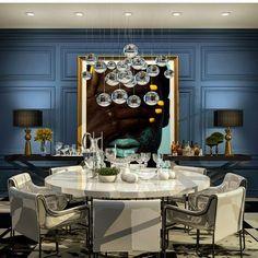 Sala de jantar com mesa e poltronas brancas, paredes azuis com moldura, abajur nos aparadores, quadro e lustre central.