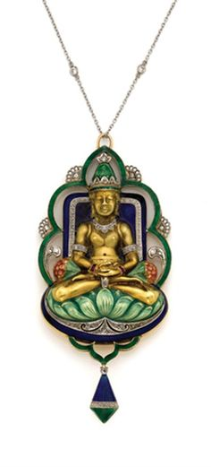 Gold, Platinum, Enamel and Diamond Buddha Pendant with Platinum and Diamond Chain   The gold buddha, seated cross legged on a green enamel cushion, arms folded in his lap, accented by ruby bracelets and diamond arm bands, his neck draped in a diamond necklace, his head topped by a green enamel and diamond crown, seated in front of a deep blue enamel background, enclosed by a scalloped green enamel and diamond frame, suspending a blue and green enamel and diamond pendant, circa 1920