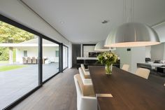 Gorgoues, long and open dining room with large wooden dining table and white dining chairs. By architecten White Dining Chairs, Wooden Dining Tables, Corporate Office Design, Villa, Best Dining, Bungalow, Ramen, House Plans, Interior Design
