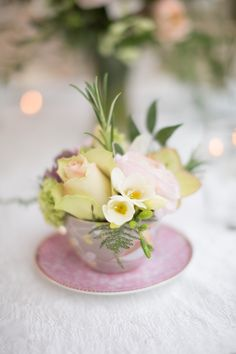 Lamber de Bie florist used a number of vintage porcelain tea cups as containers for the romantic wedding table settings. Using soft pink flowers and fresh herbs.