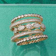 Set of Five Stackable Diamond Eternity Bands. A chic assortment of multi-shaped .88 ct. t.w. diamond bands. 14kt yellow gold rings. (=)