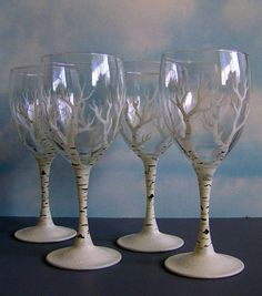 Set of four wine glasses painted to resemble graceful bare-branched birch trees in winter. Each glass is hand painted and completely unique. Feet are
