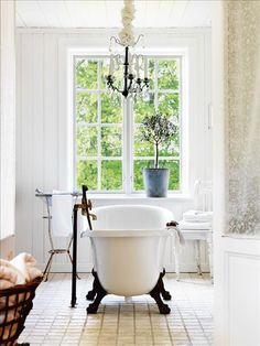 Mitt på golvet i det ljusa badrummet står badkaret i gjutmarmor på tassar, från Westerbergs. Fredrik...