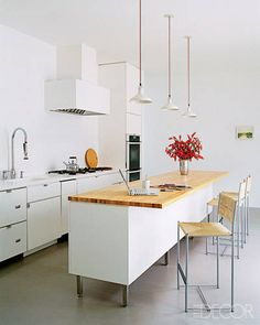 White Magic - modern kitchen featuring a wood-topped island - adding natural warmth.