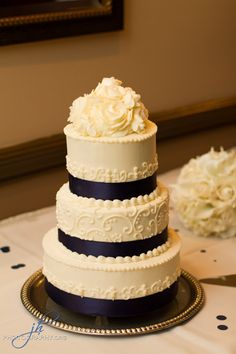 Beautiful wedding cake made from in-house pastry chef Lindsay. Three tiered wedding cake with purple ribbon, piping and hand-crafted flowers to act as the topper