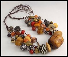 Necklace pictured has been sold, but I can make another that will be very similar. I have used a very old, hand carved wooden African spindle whorl as focal point of this dramatic necklace. 5 strands of mixed handmade African beads....clay, amber resin, brass, carved bovine bone, etc etc are double hand knotted on linen cord. Length can be adjusted so that it can be worn as standard length necklace and also as a long necklace. Ties behind neck so that everyone can find perfect length. I have…