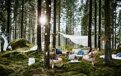 A lounge area in a forest wedding with rattan armchairs, lots of cushions and lighting chains next to a DIY photobooth