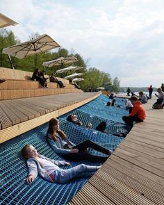 Paprocany Lake Shore Redevelopment: The waterfront site is a part of a large recreational redevelopment of a lake shore area in Poland. Wood decked walkways guide people through the space while offering sunken seating made of comfortable hammock like netting. Walkways are al...