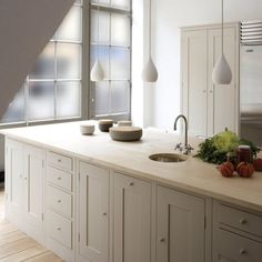 Bespoke kitchen cabinets painted dove gray (or similar) with pale wood or honed stone counter top, stainless sink, appliances, fixtures. Milk glass tear drop lights. Simply elegant.