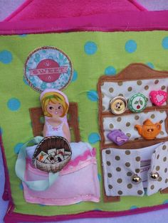 Dollhouse quiet book dining room page. Cabinet has lots of decorative buttons and the cupboard doors open to reveal an elastic pocket that holds a tablecloth which velcros onto the table. Lots of food is on ribbons in a hidden pocket and can be attached with velcro to the table or tablecloth. The doll fits in the pocket so she can sit at the table. https://www.facebook.com/sparklesandstring