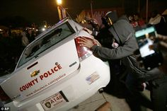 A group of protesters vandalize a police vehicle after the announcement of the grand jury ...