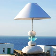 Like water over white sand the translucent aquamarine coloured pebble add a beautiful effect to the design of this ocean wave inspired pebble table lamp. Other beach lamps available.