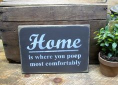 """This Wooden sign for the home is made from pine, and measures Approx 10""""W x 7.5""""H. Great housewarming gift - it reads """"Home Is Where You Poop Most Comfortably"""". The front is painted a coffee bean brow"""
