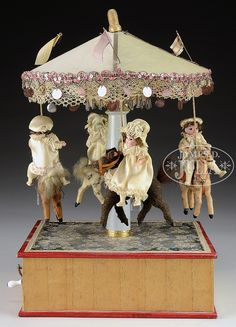 "4-HORSE WINDUP CAROUSEL WITH RIDERS. Carousel with playing music box. Underside stamped ""Made in Germany""."