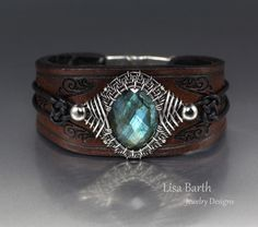 I wove a bezel with sterling wire around this Labradorite cab, then cut, dyed and tooled the leather.  It has a magnetic clasp and is lined with sheepskin.  Lisa Barth